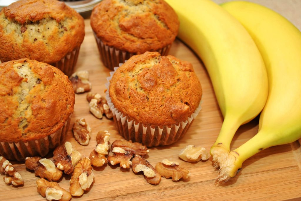 muffins on table with nuts and bananas